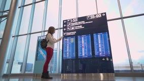 Helsinki, Finlandia - 01 14 2018: Mujer joven en el aeropuerto internacional que mira al tablero de la información del vuelo y almacen de video