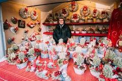 Helsinki, Finlandia Mujer que vende los regalos de los recuerdos de la Navidad en la forma de cestas de mimbre y de guirnaldas en imagen de archivo libre de regalías