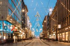 Helsinki, Finlandia Opinión de la noche de la calle de Aleksanterinkatu con el ferrocarril Imagen de archivo