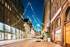 Helsinki, Finlandia Opinión de la noche de la calle de Aleksanterinkatu con el ferrocarril Fotos de archivo libres de regalías
