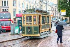 Helsinki, Finnland - touristische Tram der 12. Juni 2014, Weinlesebesichtigung im Stadtzentrum und der Fußgänger mit Regenschirm  Lizenzfreies Stockbild