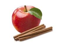 Helt nytt rött äpple och kanelbruna pinnar som isoleras på vit fotografering för bildbyråer