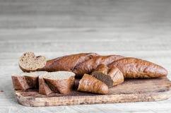 Helt och skivat bröd på en grå träbakgrund Arkivbild