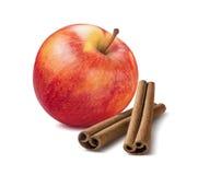 Helt rött äpple och kanelbruna pinnar som isoleras på vit fotografering för bildbyråer
