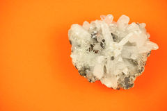 Helt stycke av vitt bildande för kvartskristall med ojämn textur, skott på apelsinpappersbakgrund Arkivfoto