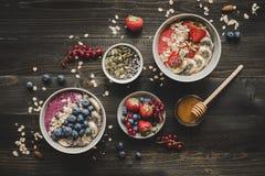 Helthy早餐可口圆滑的人滚保龄球用果子、莓果和种子在木背景 免版税库存照片