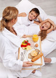Helthy breakfast in bed for the kids. A mother caring for her offsprings Stock Photos