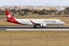 Helvetic Embraer arriving runway 31. Luqa, Malta 5 June 2016: Helvetic Airways Embraer 190LR (ERJ-190-100LR) [HB-JVL] operating a Swiss flight Royalty Free Stock Image