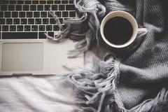 Hem- bakgrund för hemtrevlig vinter, kopp av varmt kaffe med marshmallowen, varm stucken tröja på vit sängbakgrund, royaltyfria foton