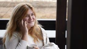 Hem- begrepp för slags tvåsittssoffa Den unga kvinnan sitter på terrass för öppet hus i pläd som talar på telefonen med en kopp k stock video