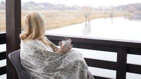 Hem- begrepp för slags tvåsittssoffa Den unga kvinnan sitter på terrass för öppet hus i pläd som tycker om väder och varmt kaffe  arkivfilmer