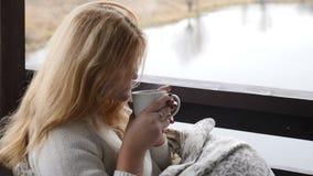 Hem- begrepp för slags tvåsittssoffa Den unga kvinnan sitter på terrass för öppet hus i pläd som tycker om väder och varmt kaffe  lager videofilmer