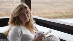 Hem- begrepp för slags tvåsittssoffa Den unga kvinnan sitter på terrass för öppet hus i pläd som tycker om varmt kaffe 4 K arkivfilmer
