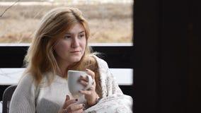 Hem- begrepp för slags tvåsittssoffa Den unga kvinnan sitter på terrass för öppet hus i pläd som tycker om varmt kaffe 4 K lager videofilmer