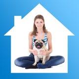 Hem- begrepp - inhyser den hållande mopshunden för den härliga kvinnan i blått fra Arkivfoto