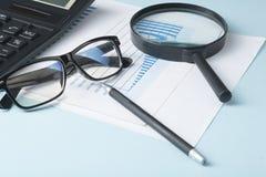 Hem- besparingar, budget- begrepp Diagram, exponeringsglas, penna, räknemaskin och förstoringsglas på träkontorstabellen Royaltyfri Bild