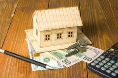 Hem- besparingar, budget- begrepp Modellera huset, pennan, räknemaskinen och mynt på den trätabellen för kontorsskrivbordet arkivfoto