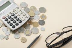 Hem- besparingar, budget- begrepp Räknemaskin, penna, exponeringsglas och mynt på en beige bakgrund Royaltyfri Foto