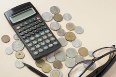 Hem- besparingar, budget- begrepp Räknemaskin, penna, exponeringsglas och mynt på en beige bakgrund Fotografering för Bildbyråer