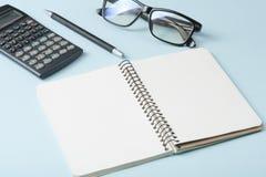 Hem- besparingar, budget- begrepp Räknemaskin, penna, exponeringsglas och notepad på kontorstabellen Royaltyfria Foton