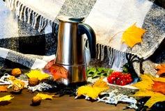 Hem- dekor för höst Metallkaffekruka under ljusa gulingsidor på den rutiga plädet Hygge stil, begrepp av komfort och hemtrevlighe arkivbilder