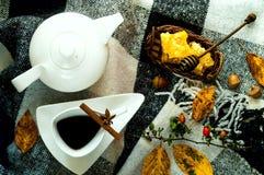 Hem- dekor för höst Vit keramisk kokkärl och tappningkopp med te, kanelbruna pinnar, anisstjärnor och honung i honungskakor royaltyfria foton