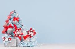 Hem- dekor för jul i pastellfärgad blå och röd färg - dekorativt julträd med bollar och gåvaaskar på det vita träbrädet royaltyfria bilder