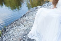 Hem dresses near the water. Dress on bride, place for text stock photos