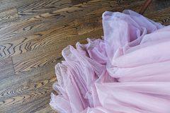 The hem of the elegant pink dress on the wooden floor, the folds of the wedding evening dress.  royalty free stock photos