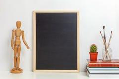 Hem- eller kontorsdekor med åtlöje upp den tomma svart tavlan på tabellen nära den vita väggen royaltyfria bilder