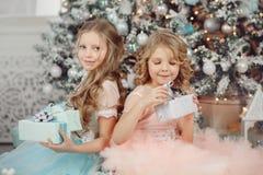 Hem för gåva för lycklig barnsyster öppet magiskt nära träd i klänning glad jul fotografering för bildbyråer