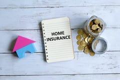 Hem- försäkring som är skriftlig på en anteckningsbok royaltyfri bild