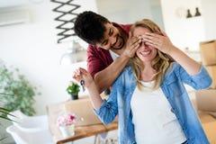 Hem-, folk-, flyttning- och fastighetbegrepp - lyckligt par som har gyckel medan inflyttning royaltyfri fotografi