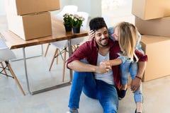 Hem-, folk-, flyttning- och fastighetbegrepp - lyckligt par som har gyckel medan inflyttning royaltyfri bild