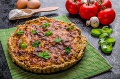 Hem- fransk paj som är välfylld med champinjoner, tomaten och purjolöken arkivfoton
