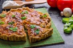 Hem- fransk paj som är välfylld med champinjoner, tomaten och purjolöken fotografering för bildbyråer