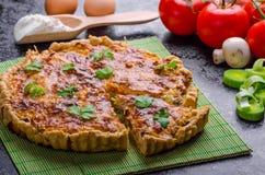 Hem- fransk paj som är välfylld med champinjoner, tomaten och purjolöken arkivbilder