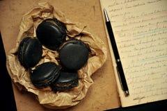 Hem- frukost med macarons och handskrivna anmärkningar Arkivfoton