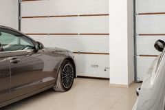 Hem- garage för två inre medel Rena lyxiga bilar parkerade hemma Automatiska fjärrkontrolldörrar Transport taklade lagring royaltyfria foton
