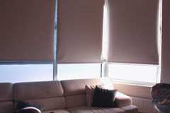 Hem- garnering med soffan och stora slutare Arkivfoto