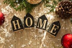 Hem- garneringar i träbakgrunden av en bokstav med ett inskrifthem Julpynt och snö Hus komfort royaltyfria foton