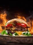 Hem gjorda hamburgare med brandflammor Royaltyfria Foton