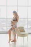 Hem- hemtrevlig stående av gravida kvinnan som hemma vilar Arkivbilder
