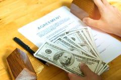 Hem- köpandebegrepp, dollar och modellhus med överenskommelsedocu Royaltyfri Foto