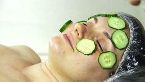 Hem- kosmetisk maskering av gurkan på flickans framsida stock video