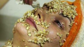 Hem- kosmetisk maskering av havremjölet på flickans framsida arkivfilmer