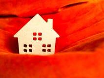 Hem- leksak för trä på livligt orange tyg Bygg hem- eller bostadslånbegreppet arkivfoton