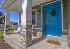 Hem med den blåa dörrgården för farstubro och det vita staketet royaltyfri foto