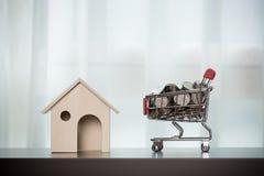 Hem och pengar i shoppingkorgen på trätabellen arkivbild