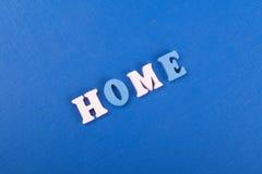 HEM- ord på blå bakgrund som komponeras från träbokstäver för färgrikt abc-alfabetkvarter, kopieringsutrymme för annonstext lära Arkivbild